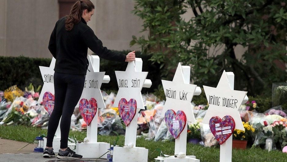 A woman touches a white Jewish star memorial for Tree of Life victim