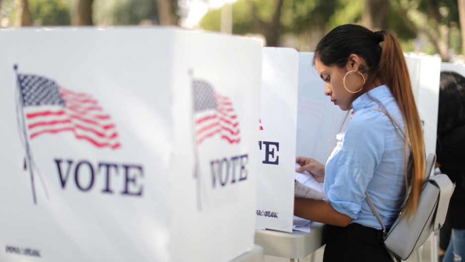"""A woman with a blue shirt and her hair pulled back is shown voting at a booth with an American flag and the word """"vote"""" on the side."""