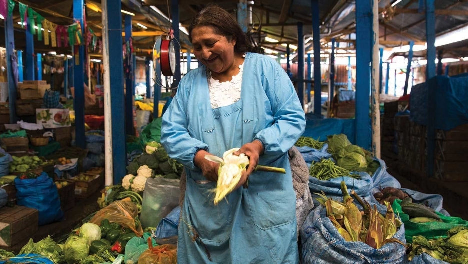 A woman wearing blue stands at her stall in the market
