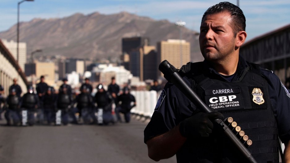 A US Custom and Border Protection agent stands in the foreground with a riffle additional agents armed in the distance.