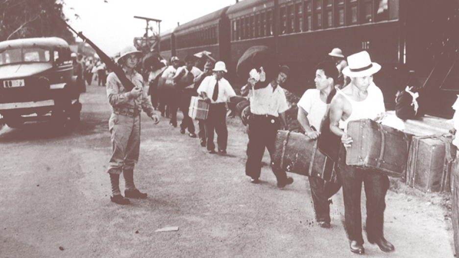 A solider with a rifle watches while men carrying suitcases line up next to a train.