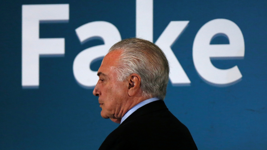 "Brazil's President Michel Temer with ""FAKE"" spelled out behind his head"