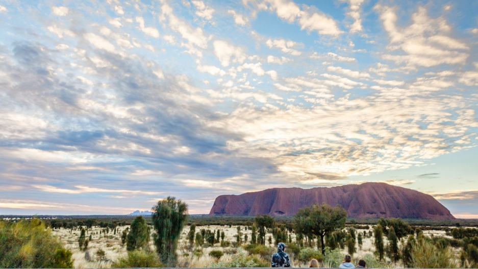 The Uluru rock formation is seen off in the distance with the sun rising across the sky.