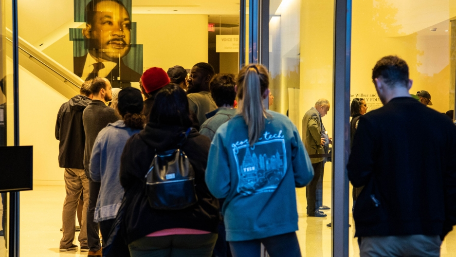 People line up in a voting queue. Above them is a portrait of Martin Luther King Jr.