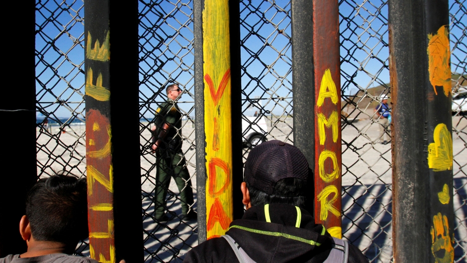 Migrants peer through a fence at a US soldier on the US side of the US-Mexico border.