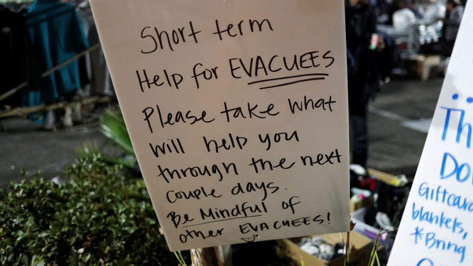 "A handwritten sign says, ""Short term help for evacuees. Please take what will help you through the next couple days. Be mindful of other evacuees!"""