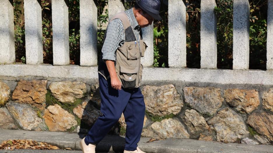 Iwao Hakamada walks in front of a fence