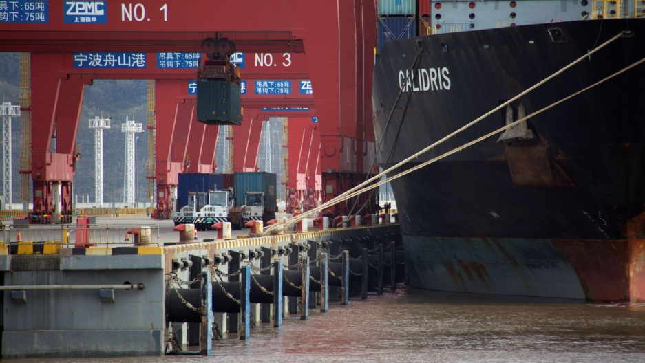 Trucks transport containers are shown being moved from trucks to a container ship at a port in China.