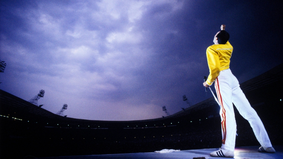 Freddie Mercury on stage wearing a yellow leather jacket and singing to the sky.