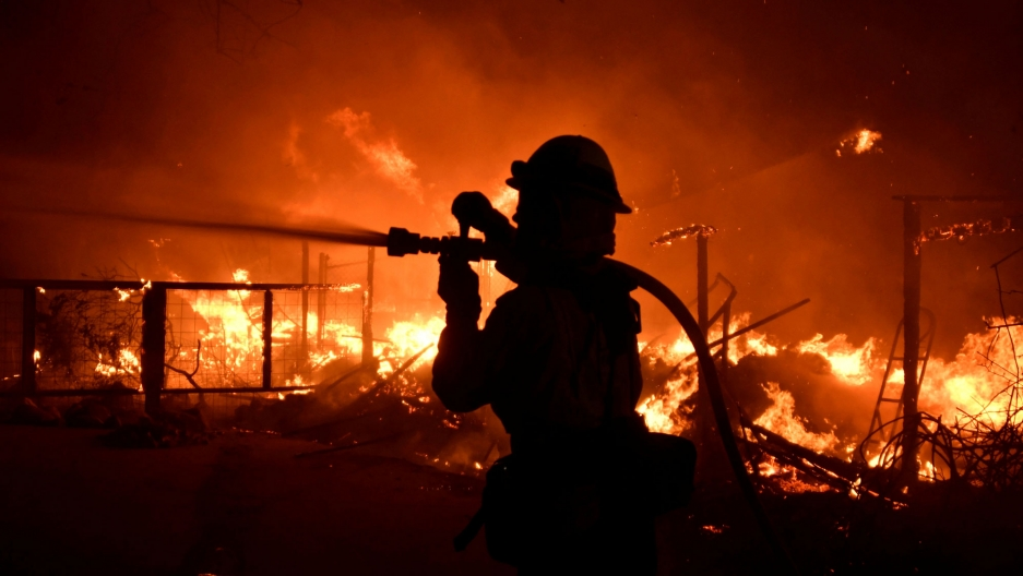 A firefighter is shown in silhouette with a hose over their shoulder and bright flames in the background.