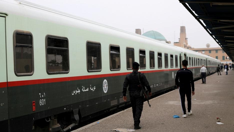 Passengers walk on a platform before boarding a train to Fallujah.