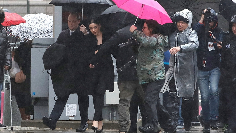 Emma Coronel Aispur is shown surrounded by several photographers walking while underneath umbrellas.