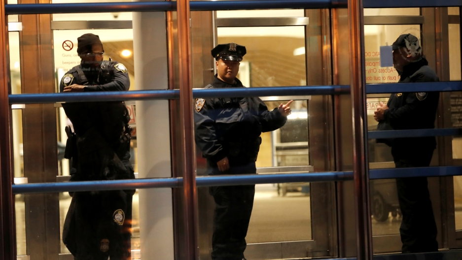 Three police stand inside the courthouse in Brooklyn