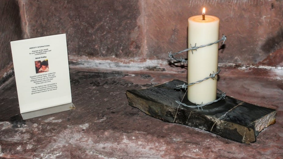 A candle surrounded by barbed wire next to a written description of Amal Fathy