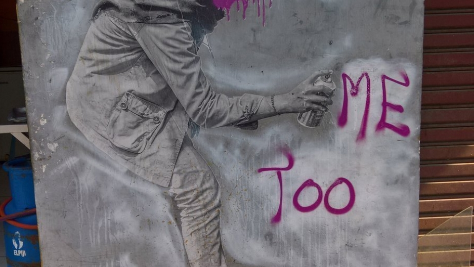 Depiction of girl wearing a hijab sprays 'me too' in pink letters