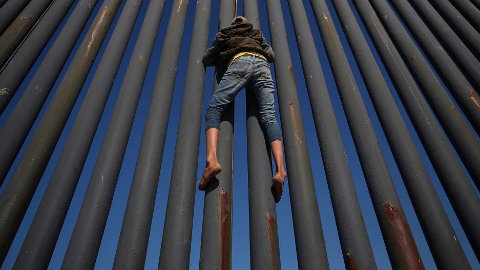 A person clings to a metal fence set against a bright blue sky.