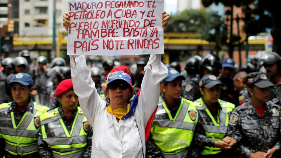 A woman holds a protest sign in Spanish.