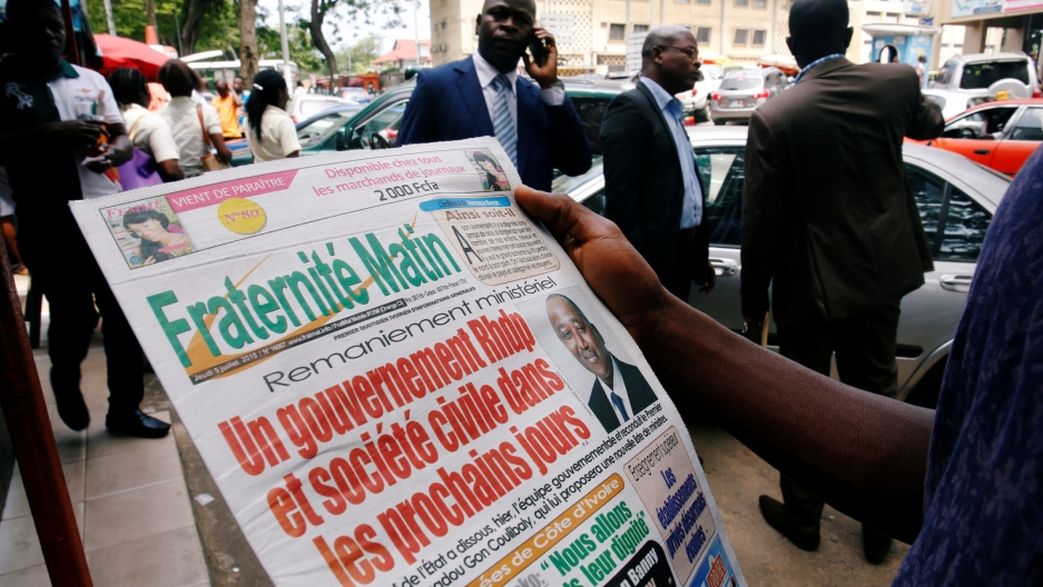 An Ivory Coast man reads a newspaper.