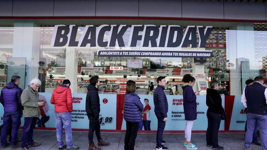 "Shoppers wait in long lines in front of a storefront window that reads ""Black Friday"" in black and white letters."