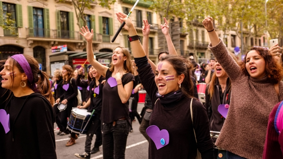 A street is shown filled with many women with arms raised rallying against prostitution.