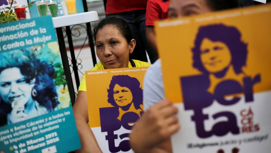 Demonstrators hold signs with Berta Cáceres' face outside a court.