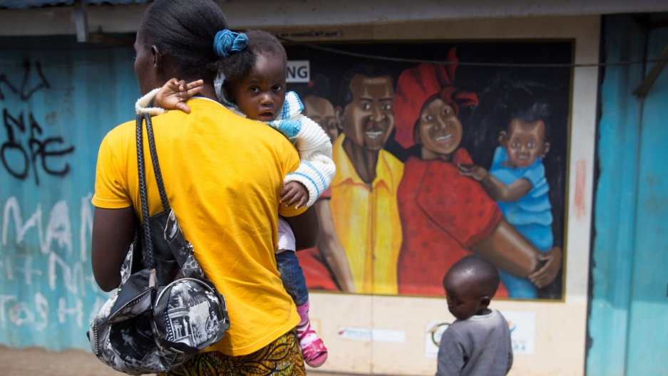 A woman wearing a yellow shirt holds a toddler in her arms near a mural.