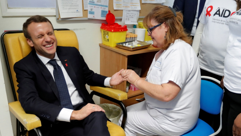 A nurse is shown taking blood for a HIV test from French President Emmanuel Macron who is sitting in a yellow chair cringing.