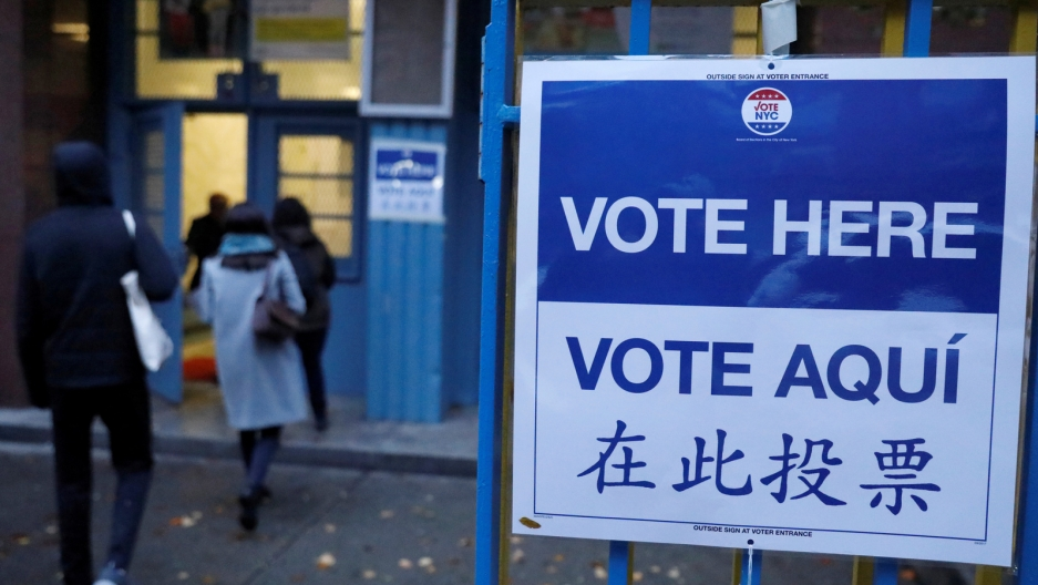 "A large blue and white sign reads ""Vote Here"" in Spanish, Chinese and English."