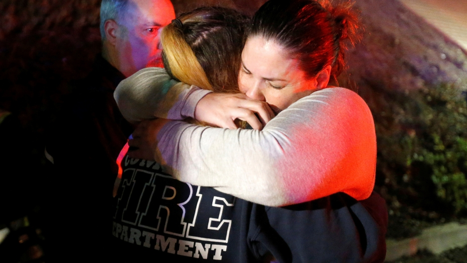 A young woman in tears hugs a police officer.