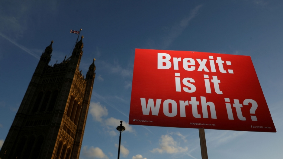 "A red placard with white lettering reading, ""Brexit: is it worth it?"" is shown in the foreground with the Houses of Parliament in the background."