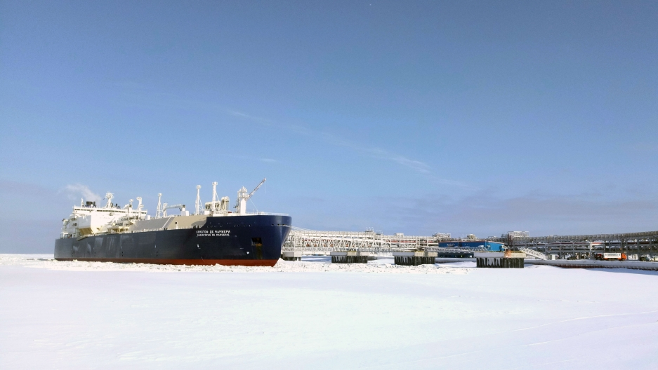 A large oil tanker docks amid ice and snow in the Arctic. On the side, the ship's name is written in Russian characters.