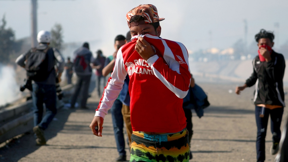 A man uses his shirt to cover his face as he runs from tear gas