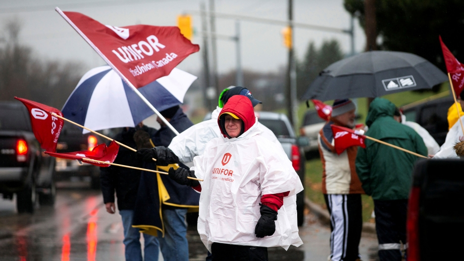 "A person waves a red flag with the words ""Unifor"" on it with a group of others alongside a road."