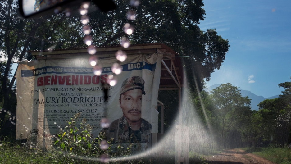 "A sign seen through a windshield says ""Welcome."" It is marking the entrance to a FARC camp in Colombia."