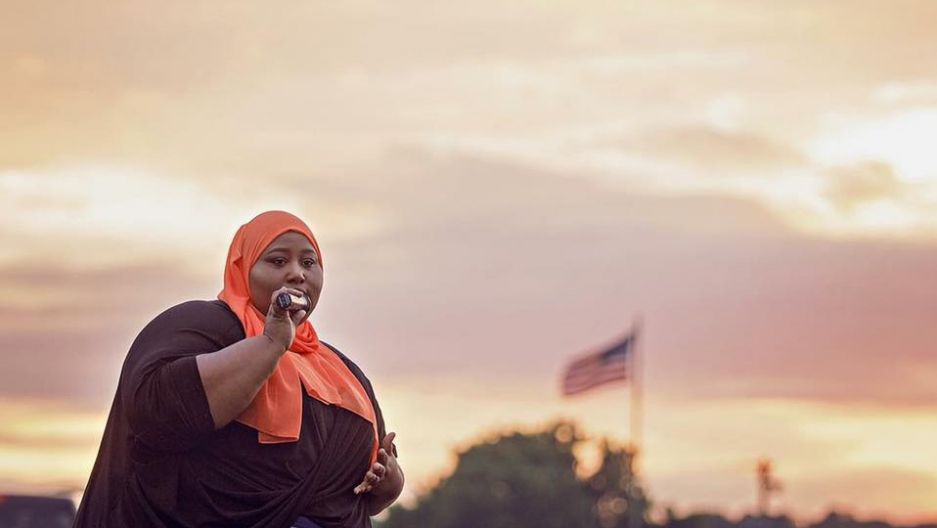A woman in a hijab speaks into a microphone as dawn breaks in the clouds. An American flag waves in the distance.