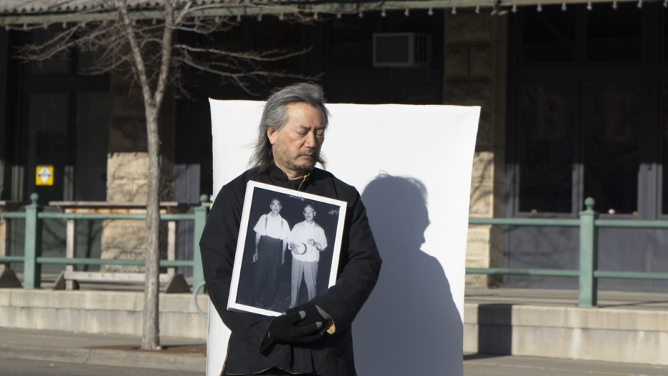 A man stands outside holding a photograph in front of a white sheet