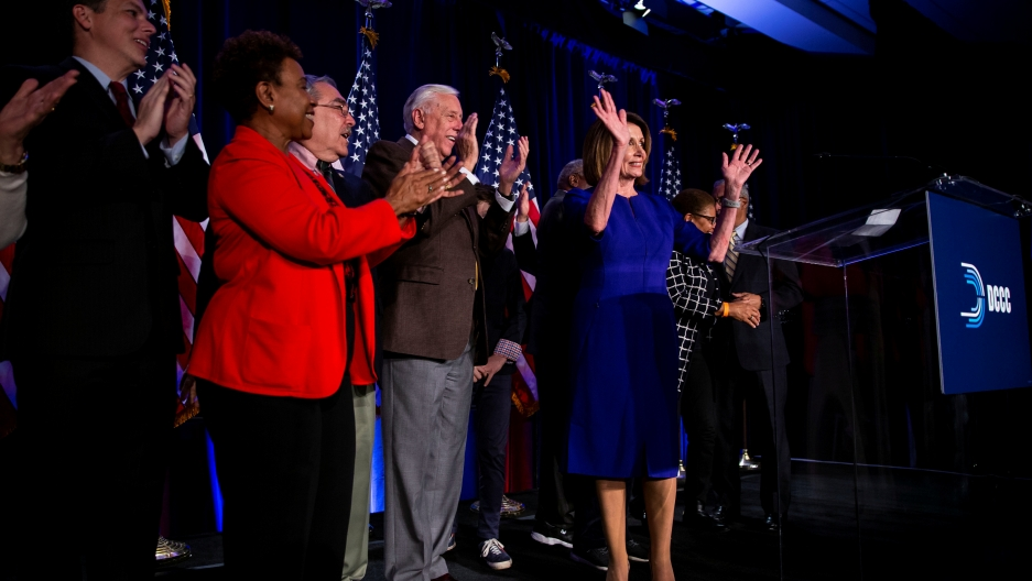 several house democrats celebrating on a stage after their majority house win