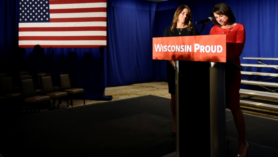 "Two women stand at podium, sign reads, ""Wisconsin Proud"""