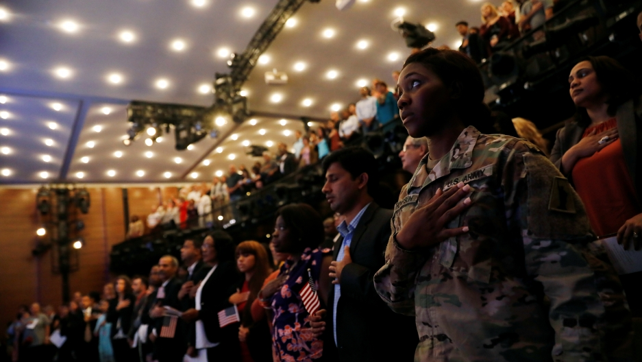 New citizens stand during the National Anthem at a U.S. Citizenship and Immigration Services naturalization ceremony
