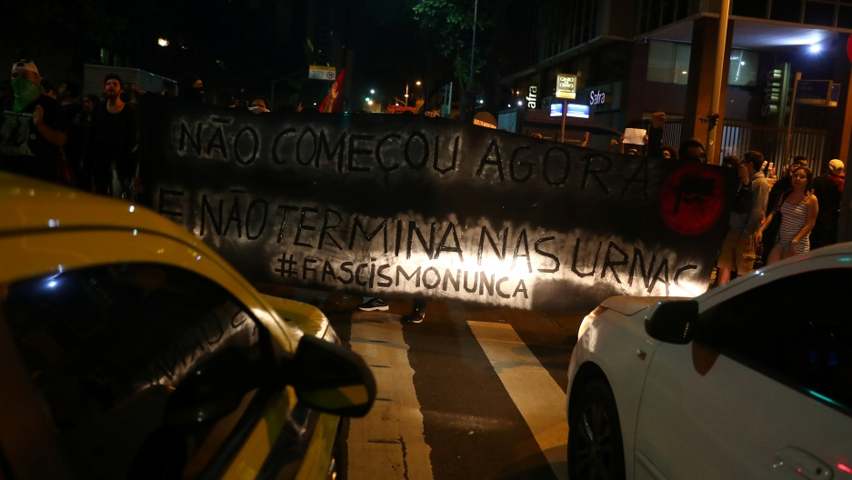 two cars flash their lights on a sign held by anti-Bolsonaro protesters