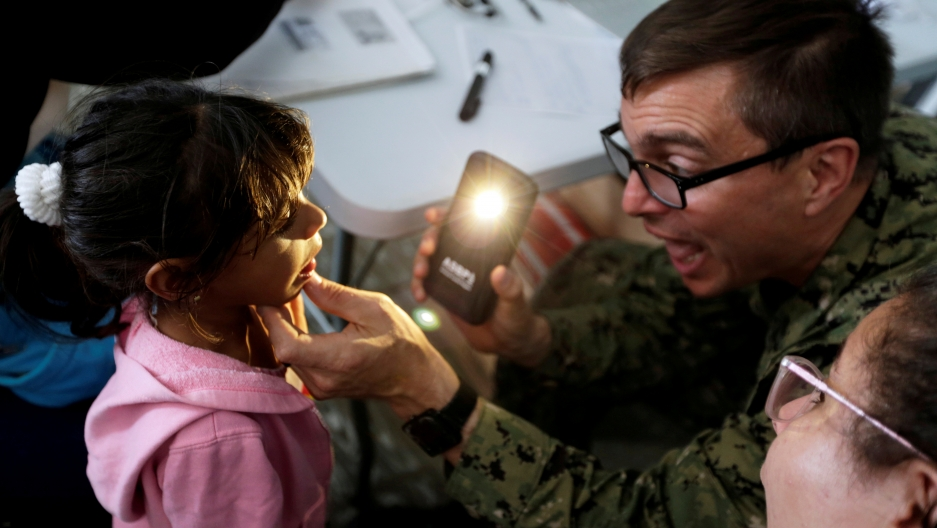 a doctor shining a light into a young girl's mouth