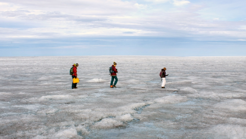 Three people walk across ground covered in ice and snow as the horizon stretches behind them.