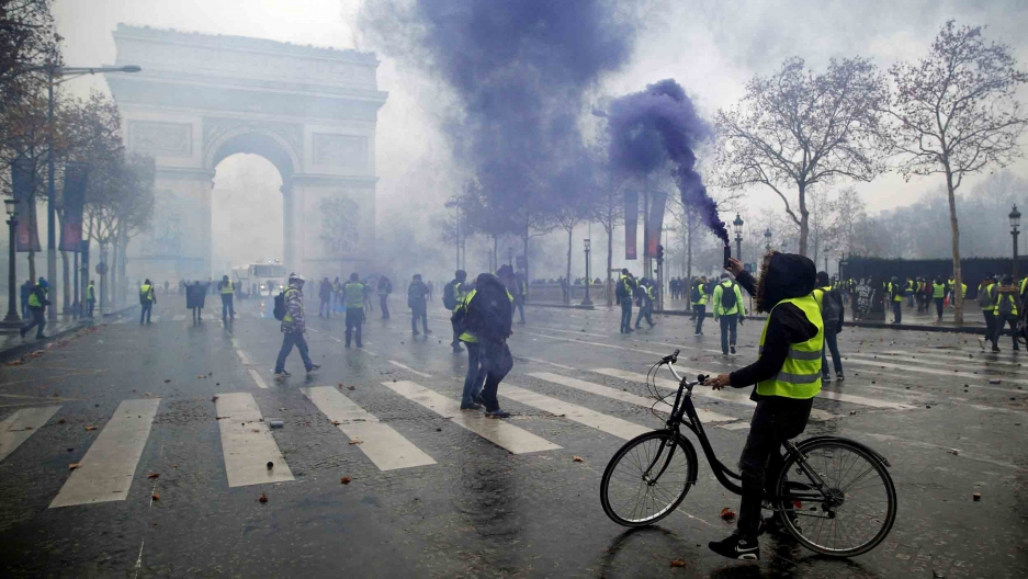 A man stands on a bicycle with a smoke flare in his hand, wearing a bright yellow vest in the street before the Arc de Triomphe. About 50 others also wearing yellow vests are also in the street.