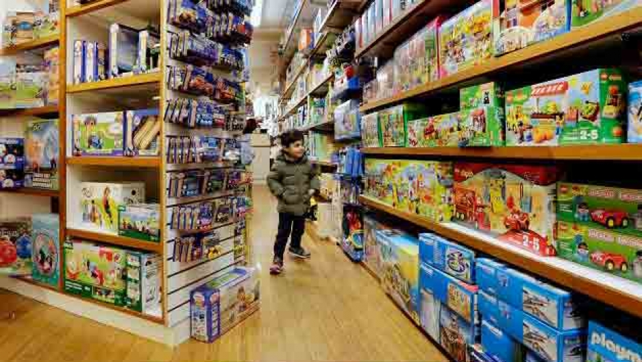 A child stands in a store looking at an array of plastic toys in colorful boxes.