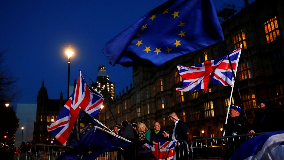 British flags wave against a dark sky outside the Parliament building in Long. People stand behind iron barricades holding the flags.