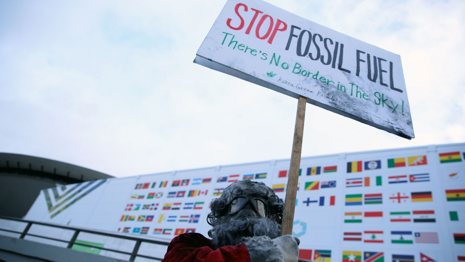 "A man wearing googles holds up a sign that says ""stop fossil fuel! there is no border in the sky!"""