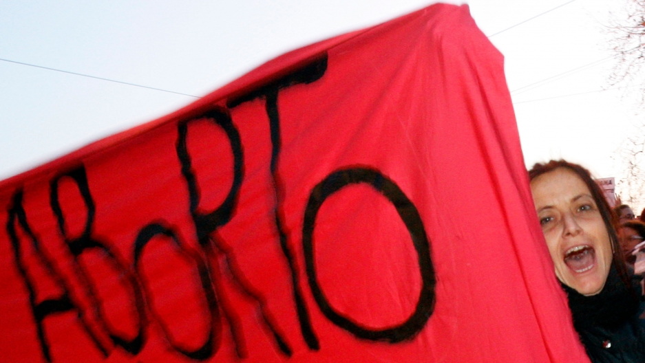 """A woman's face looks out from behind a red protest banner that says """"aborto"""""""
