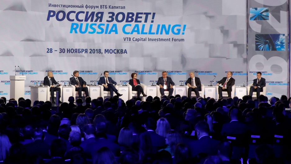 "A line of people sit on a panel in front of a large crowd. Behind them, the backdrop says ""Russia calling!"""