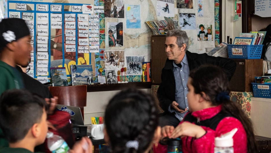 Host Marco Werman looks on as children from a fourth grade class in East Boston discuss a poem written on a white board.