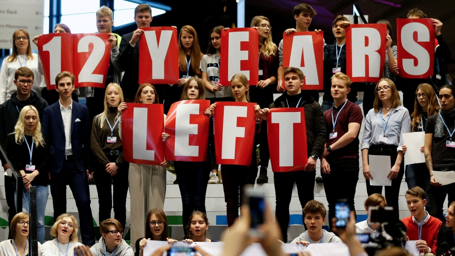 "A group of school children hold signs that read ""12 years left"""